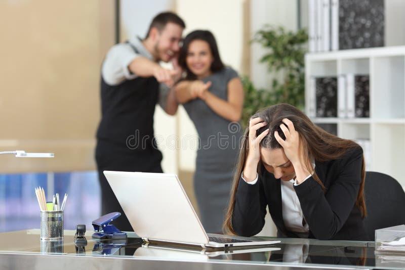 Empresários que tiranizam um colega no escritório foto de stock