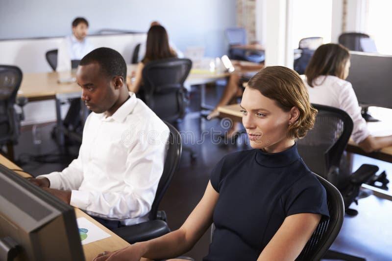 Empresários que trabalham em computadores no escritório moderno ocupado foto de stock royalty free