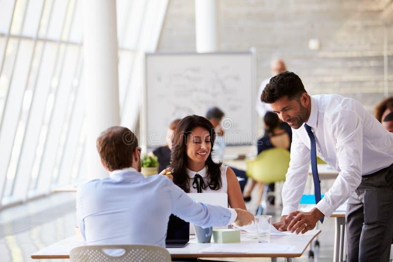 Empresários que trabalham em mesas no escritório moderno fotos de stock