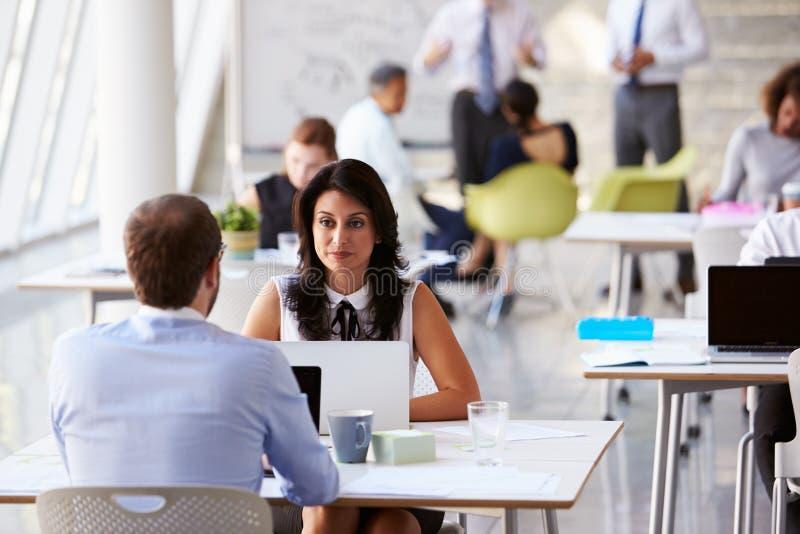 Empresários que trabalham em mesas no escritório moderno fotos de stock royalty free
