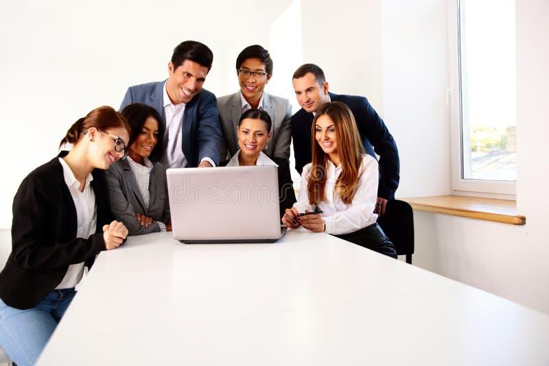 Empresários que trabalham no portátil na reunião imagem de stock royalty free