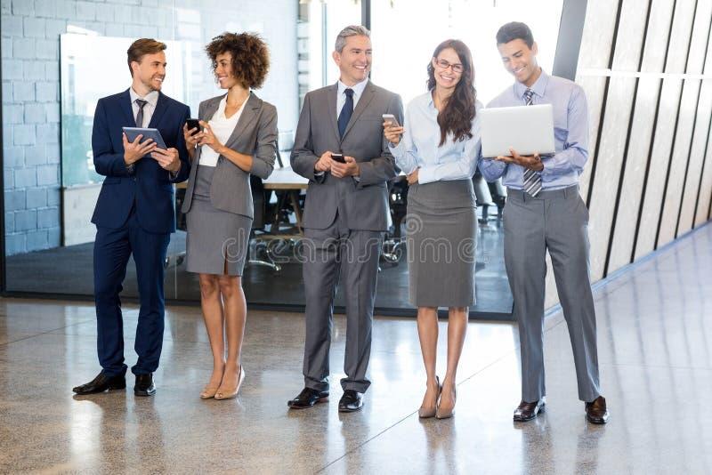 Empresários que usam o telefone celular, a parte superior do regaço e a tabuleta digital foto de stock