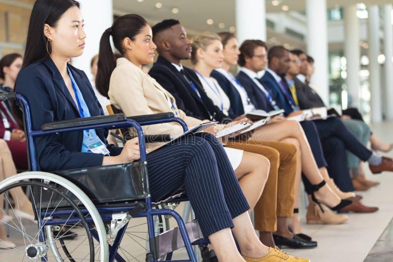 Empresários sentados em cadeiras enquanto ouvem o discurso fotos de stock