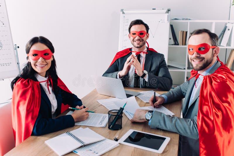 empresários super de sorriso nas máscaras e cabos que sentam-se na tabela fotografia de stock royalty free