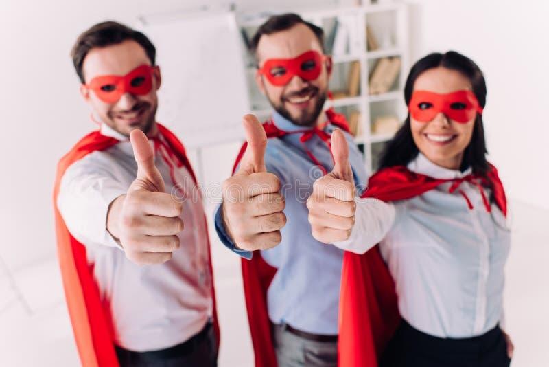 empresários super nas máscaras e cabos que mostram os polegares acima ilustração royalty free