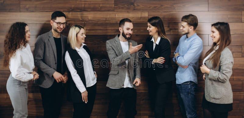 Empresa bem sucedida com os trabalhadores felizes que estão na fileira no escritório moderno fotografia de stock