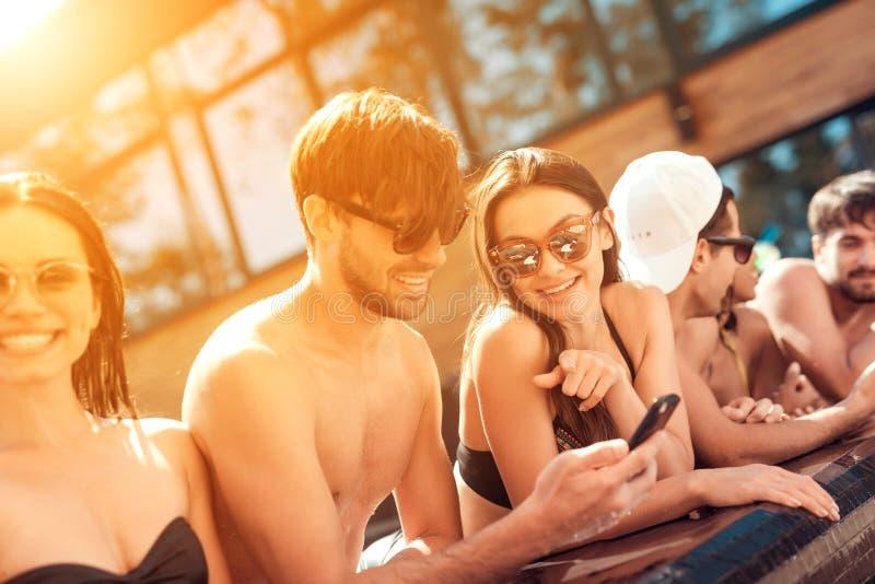 A empresa de amigos novos olha as fotos tomadas no smartphone na associação no verão fotos de stock
