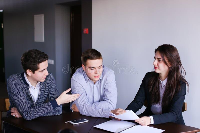 A empresa dos agentes de seguros das mulheres e dos homens prepara a opinião sobre foto de stock