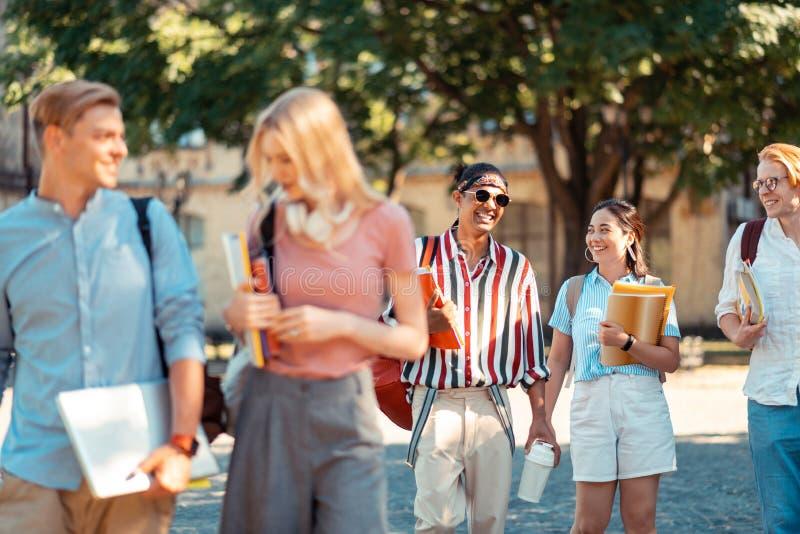 Empresa dos estudantes alegres que vão em casa junto foto de stock