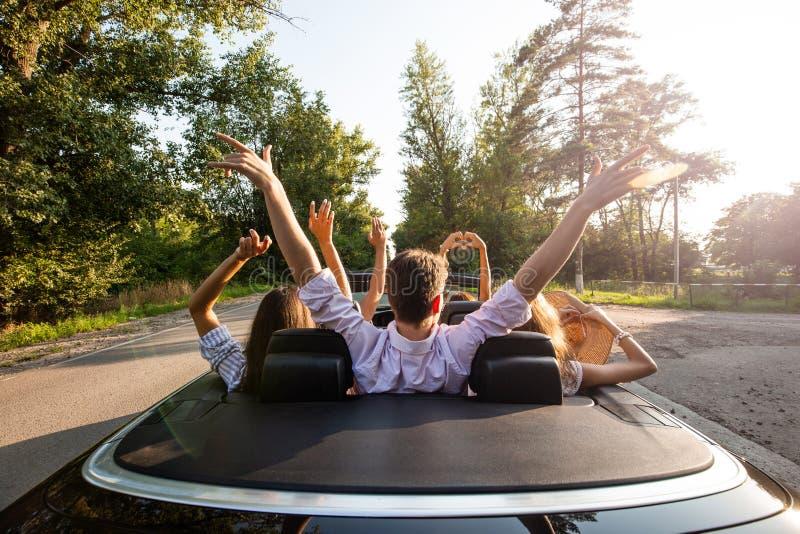 Empresa dos jovens que montam em um cabriolet na estrada e que guardam suas mãos acima em um dia ensolarado morno Vista traseira foto de stock