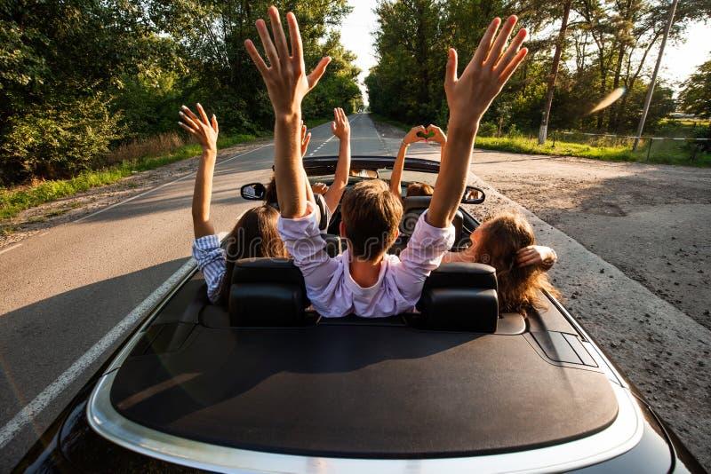 Empresa dos jovens que montam em um cabriolet na estrada e que guardam suas mãos acima em um dia ensolarado morno Vista traseira imagem de stock