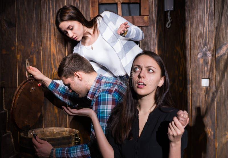 Empresa dos jovens que tentam resolver um enigma para sair do foto de stock