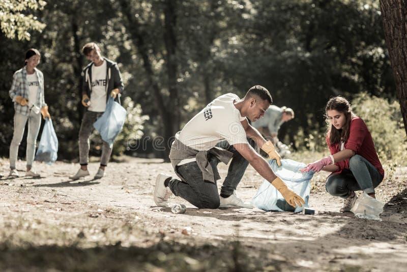 A empresa dos voluntários diligentes que trabalham limpando o lixo saiu na floresta fotos de stock