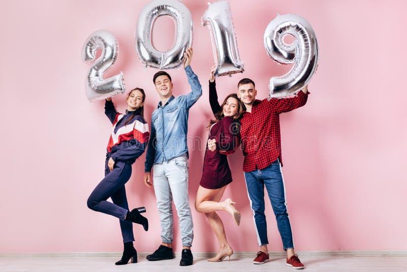 A empresa feliz de duas meninas e dois indivíduos vestidos na roupa à moda estão guardando balões na forma dos números 2019 foto de stock
