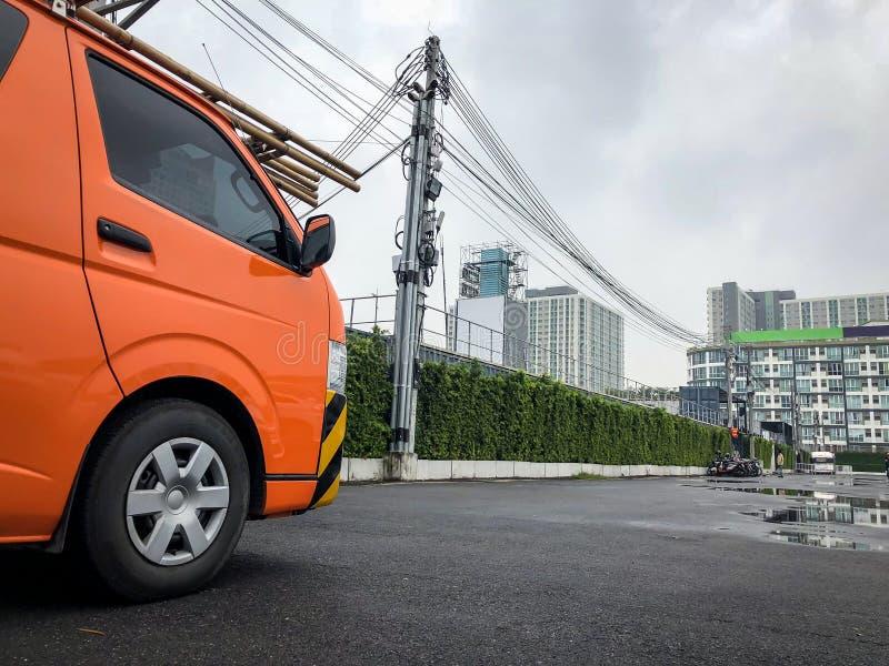Empresa privada camionete alaranjada elétrica estacionamento nos serviços elétricos de espera do estacionamento exterior imagens de stock royalty free