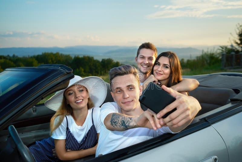 Empresa que faz o selfie ao sentar-se no cabriolet fotos de stock