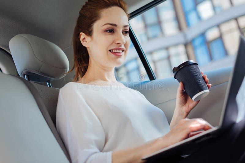 Empresaria acertada atractiva que sostiene una taza de café imagen de archivo libre de regalías