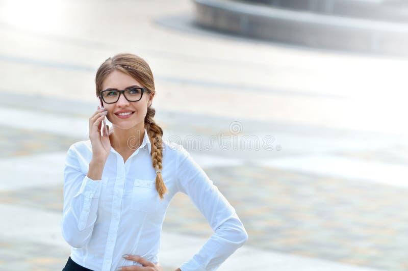 Empresaria acertada que habla en el teléfono móvil mientras que camina al aire libre foto de archivo