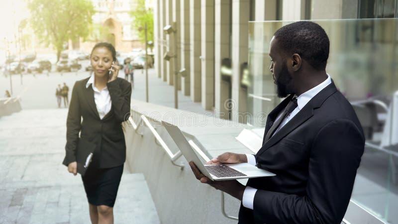Empresaria acertada que pasa por el hombre de negocios negro hermoso, afecto fotos de archivo libres de regalías