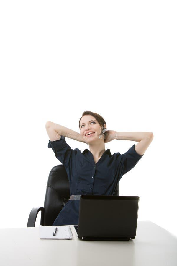 Empresaria acertada que se relaja en su escritorio fotos de archivo