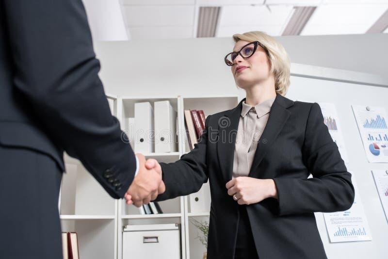 Empresaria acertada Shaking Hands con el socio imagenes de archivo