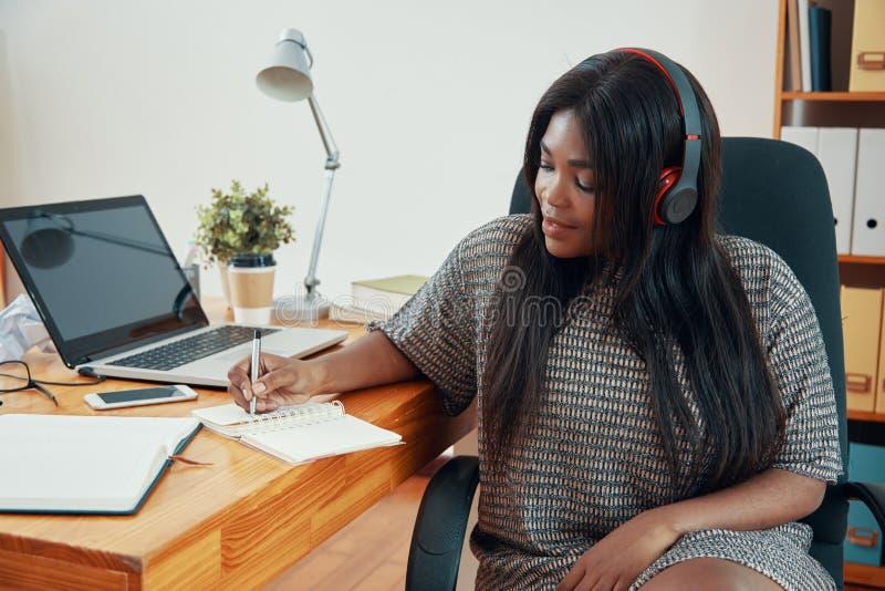 Empresaria adulta en los auriculares que toman notas imagenes de archivo