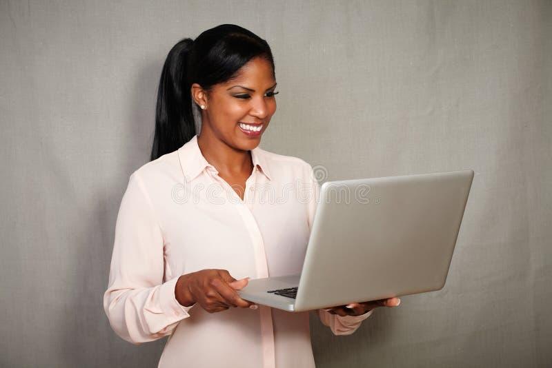 Empresaria africana joven que usa un ordenador portátil imagenes de archivo