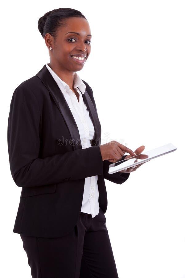 Empresaria africana sonriente que usa una tablilla imagenes de archivo