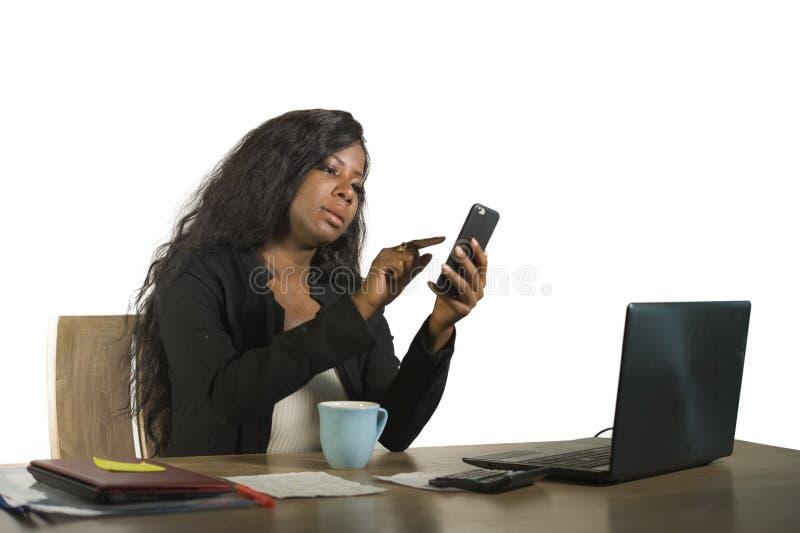 Empresaria afroamericana negra hermosa y ocupada joven que usa el teléfono móvil que trabaja en el escritorio con el ordenador po imagen de archivo libre de regalías