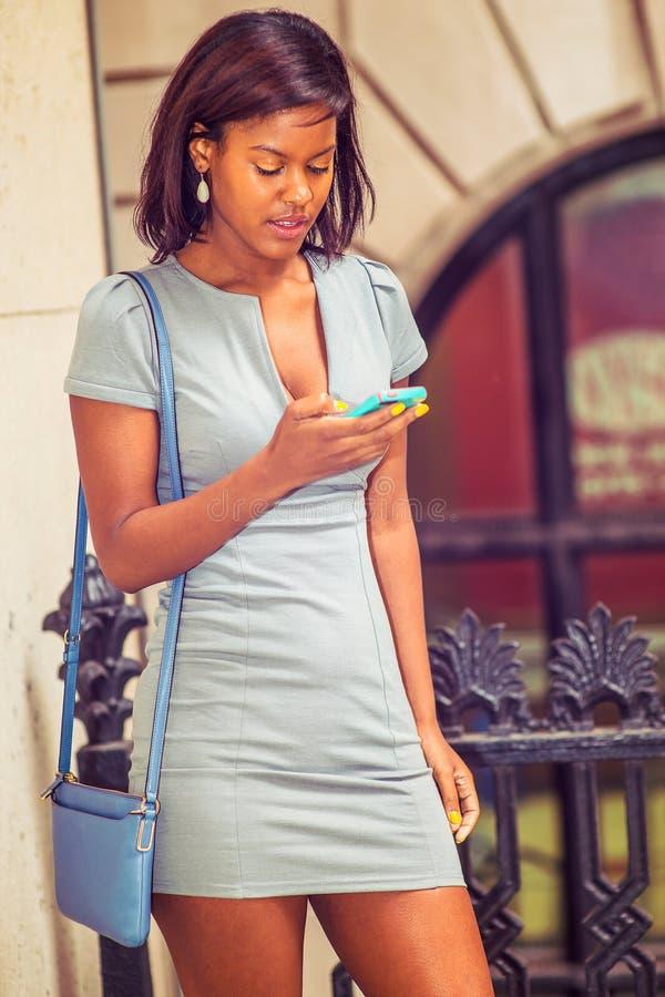 Empresaria afroamericana que manda un SMS a la oficina exterior en nuevo Yor imagenes de archivo