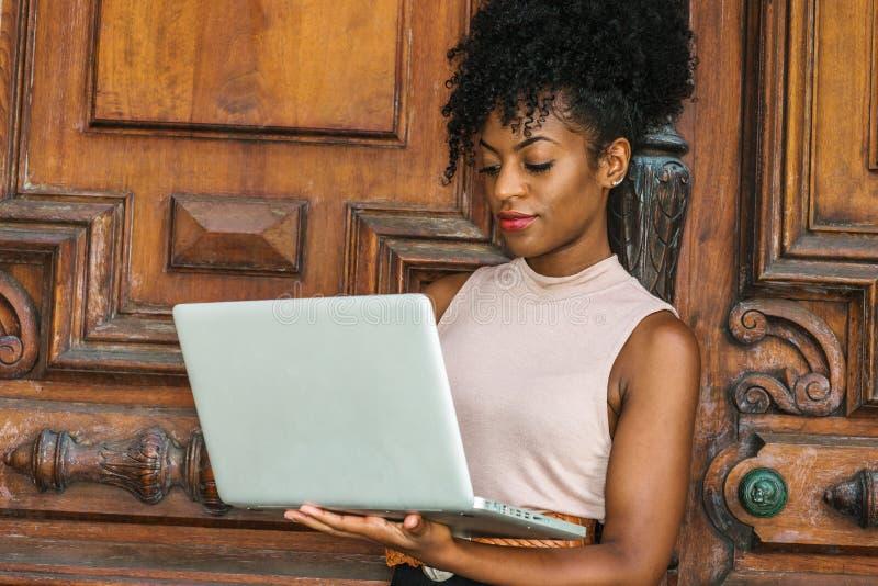 Empresaria afroamericana que trabaja en Nueva York Mujer negra hermosa joven con el peinado afro que lleva color claro sin mangas fotografía de archivo