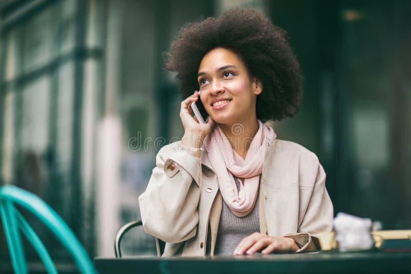 Empresaria afroamericana sonriente joven que invita a smartphone foto de archivo
