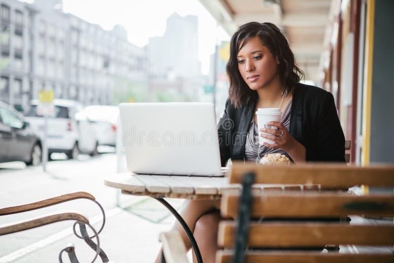Empresaria afroamericana trabajando en su laptop en un café al aire libre fotografía de archivo