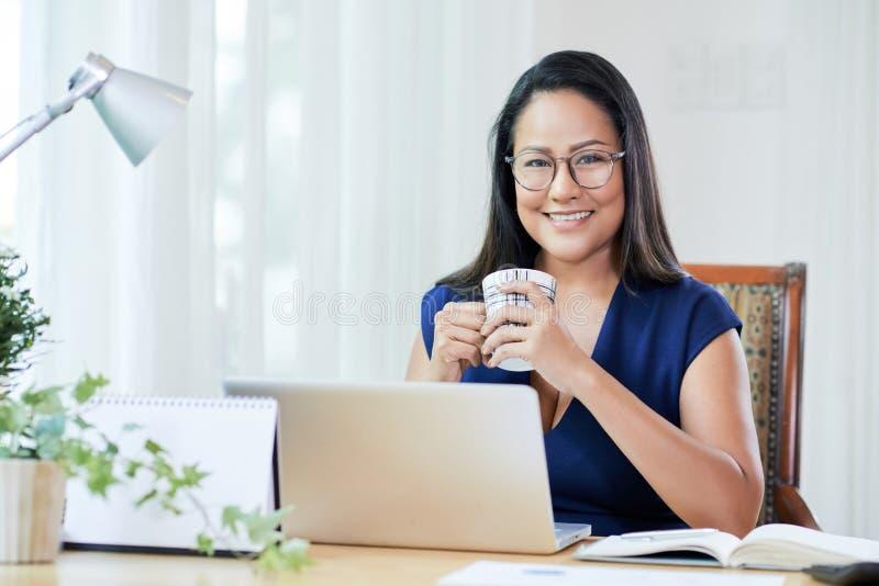 Empresaria alegre con café en el escritorio de trabajo foto de archivo libre de regalías