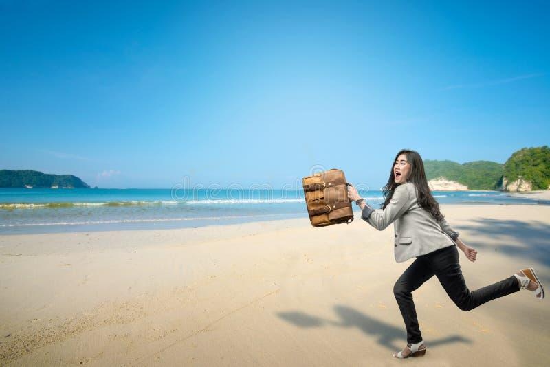 Empresaria asiática alegre con vacaciones que van de la cartera a la playa fotografía de archivo