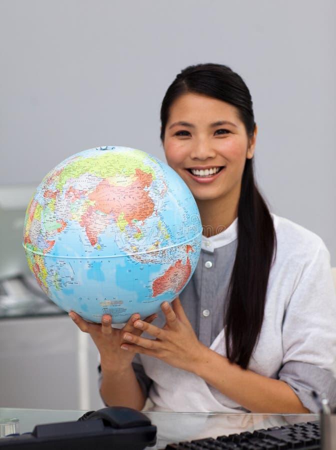Empresaria asiática asertiva que sostiene un globo imagen de archivo