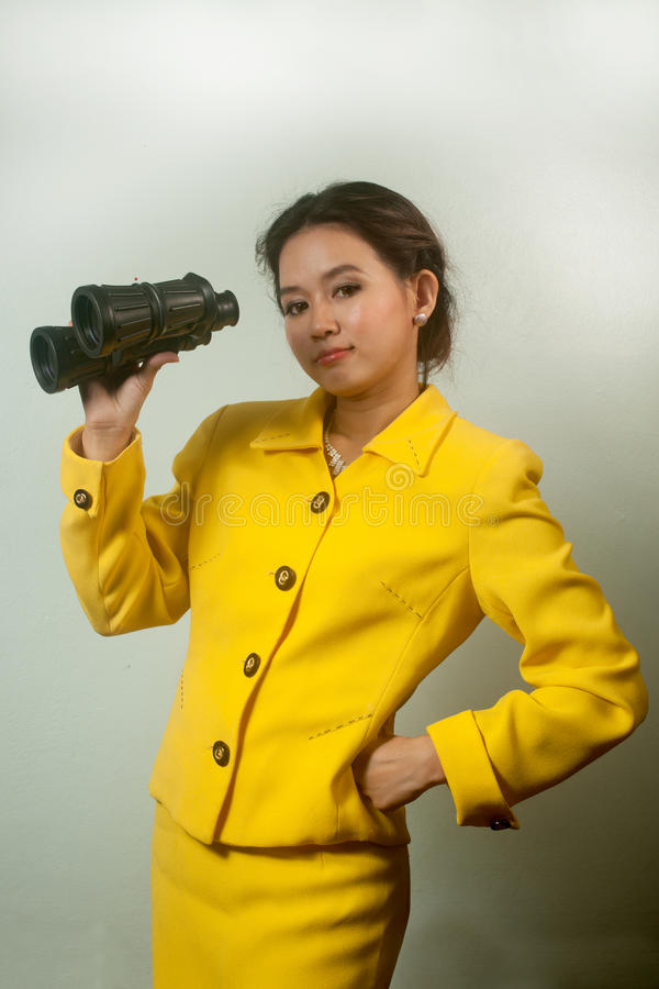 Empresaria asiática bastante joven en el traje amarillo sosteniendo los prismáticos. foto de archivo