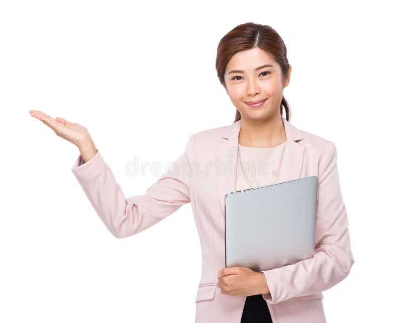 Empresaria asiática con el ordenador portátil y la mano presentes imagen de archivo
