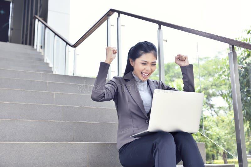 Empresaria asiática feliz con el funcionamiento del ordenador portátil imagenes de archivo