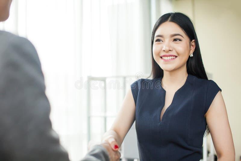 Empresaria asiática hermosa que sonríe y que sacude las manos imagen de archivo libre de regalías