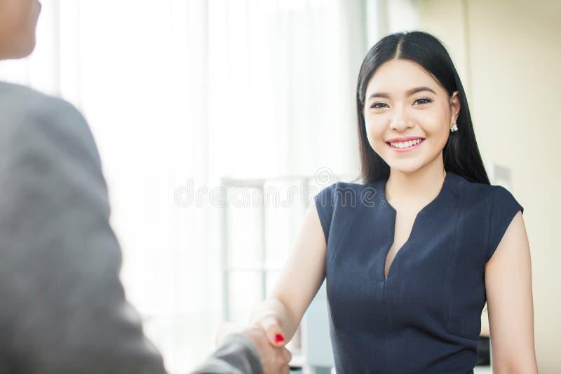 Empresaria asiática hermosa que sonríe y que sacude las manos foto de archivo