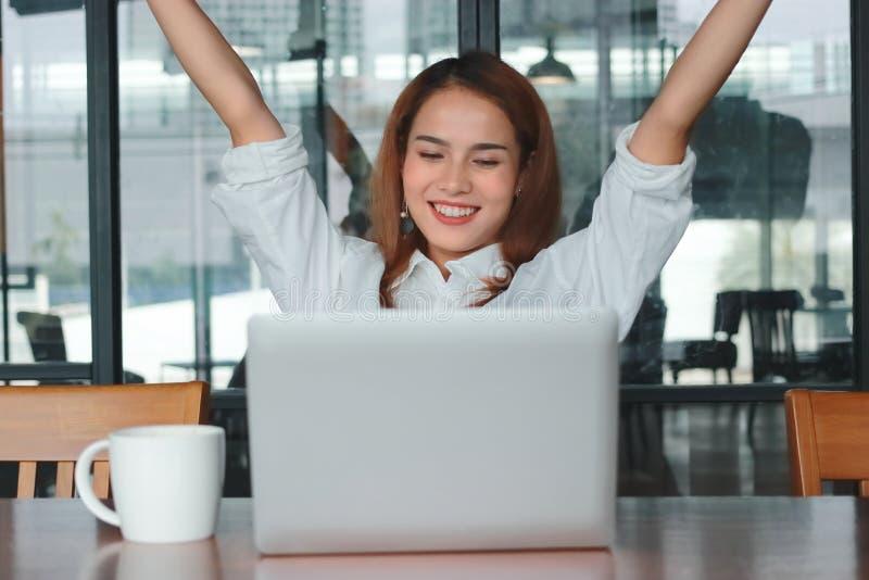 Empresaria asiática joven alegre acertada con el ordenador portátil que aumenta las manos en oficina Pensamiento y concepto pensa fotos de archivo libres de regalías