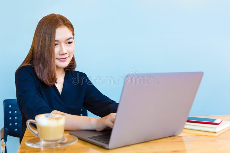 Empresaria asiática joven atractiva feliz que trabaja en su ordenador portátil fotografía de archivo libre de regalías