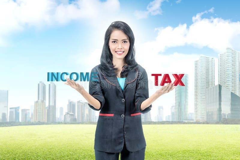 Empresaria asiática joven equilibrio entre la renta y el impuesto imagen de archivo libre de regalías