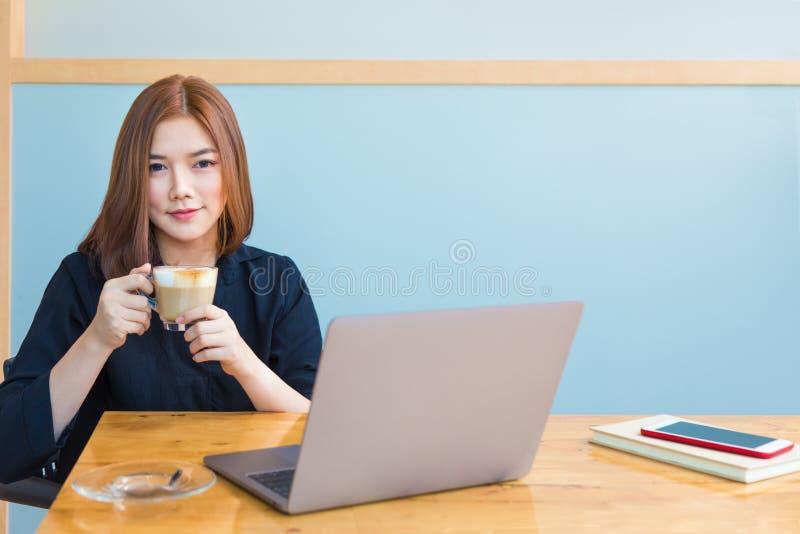 Empresaria asiática joven feliz que goza de su café caliente mientras que wo fotografía de archivo