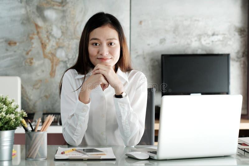 Empresaria asiática joven que trabaja con con la cara sonriente en el offi foto de archivo libre de regalías