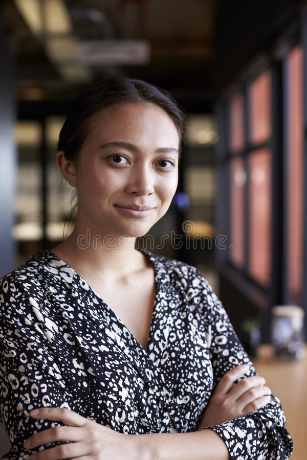 Empresaria asiática milenaria por la ventana en una oficina que sonríe a la cámara, cintura para arriba, vertical imágenes de archivo libres de regalías
