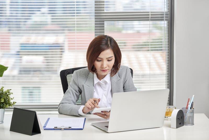 Empresaria asiática o contable que señala gráficos de discusión y análisis de datos gráficos y gráficos y que utiliza una c imagen de archivo libre de regalías