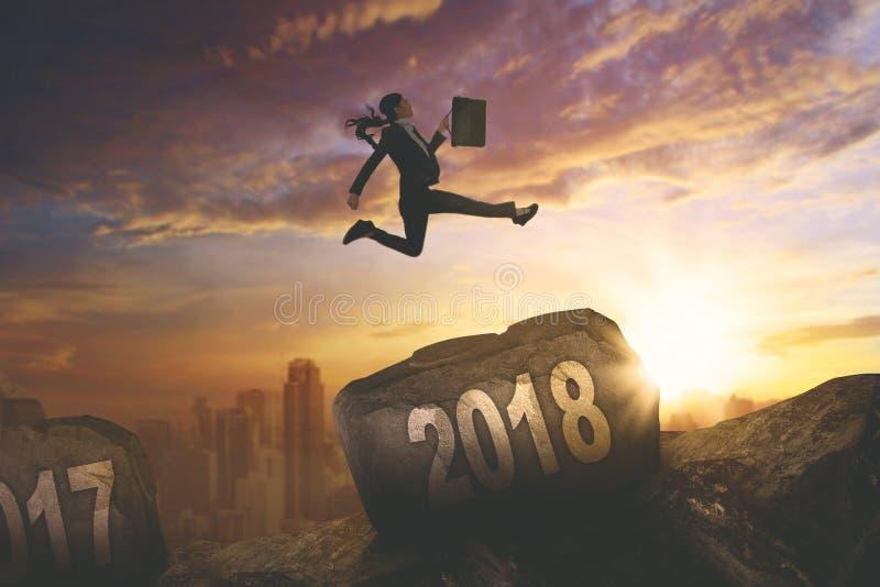 Empresaria asiática que salta sobre el número 2018 imagenes de archivo