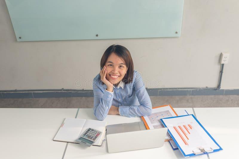 Empresaria asiática sonriente que trabaja en el cuarto del negocio imagen de archivo